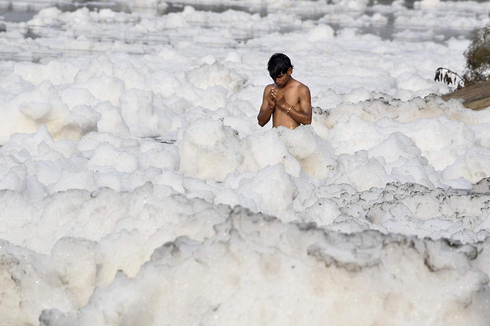 מוקף בקצף: ילד מתפלל בנהר היאמונה המזוהם בניו דלהי, הודו (צילום: AFP)
