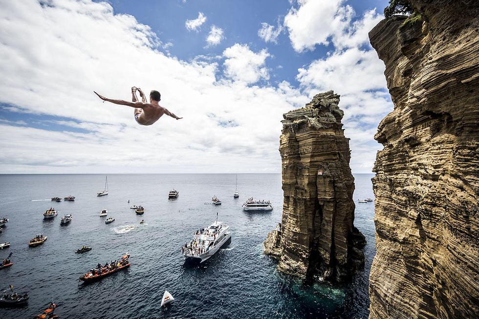 """ילד קופץ למים מצוק בתחרות עולמית של """"רד בול"""" באי סאו מיגל, פורטוגל (צילום: gettyimages)"""