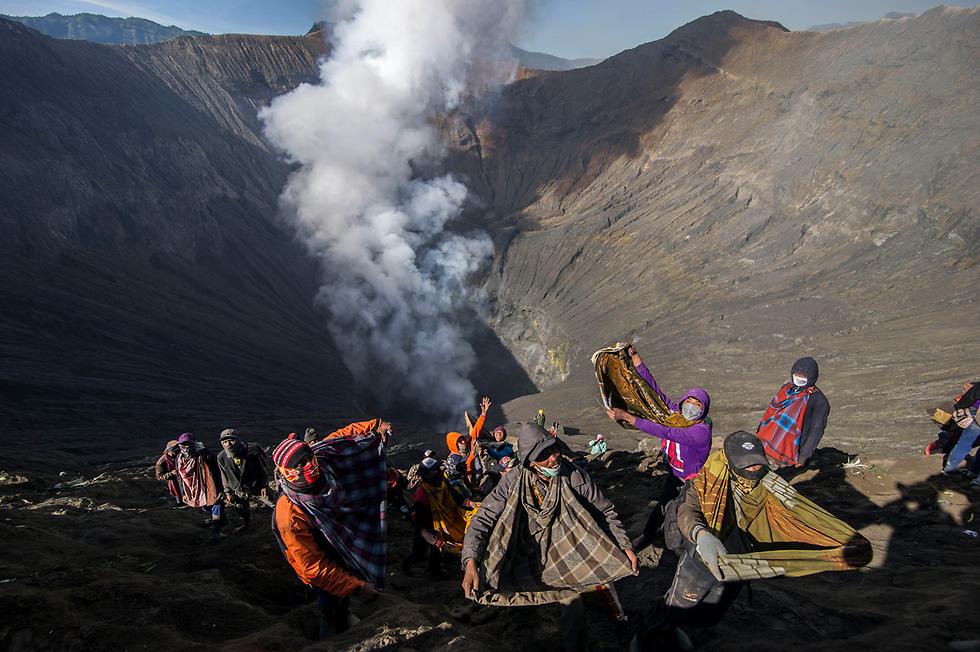 כפריים תופסים מנחות שמושלכות להר הגעש ברומו באינדונזיה (צילום: AFP)