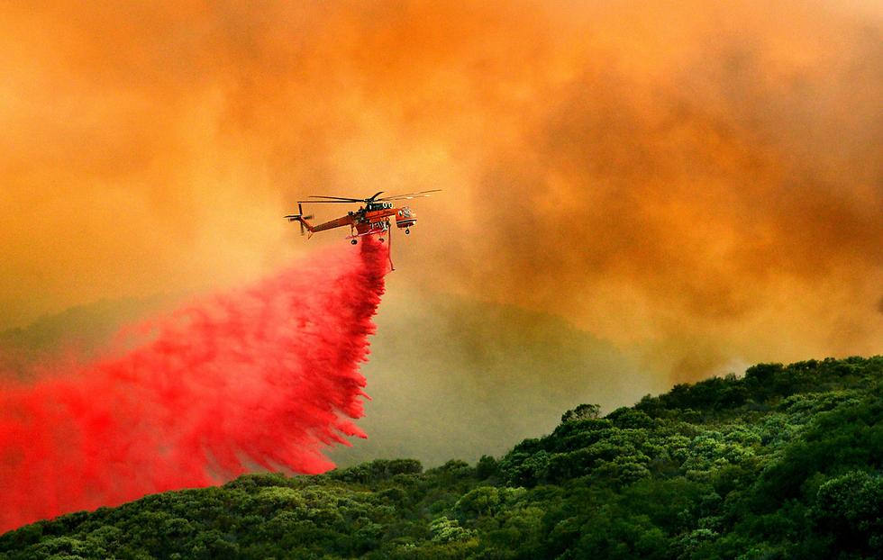מסוק מפזר חומר מעכב בעירה בשרפה בסנטה ברברה, קליפורניה (צילום: EPA)