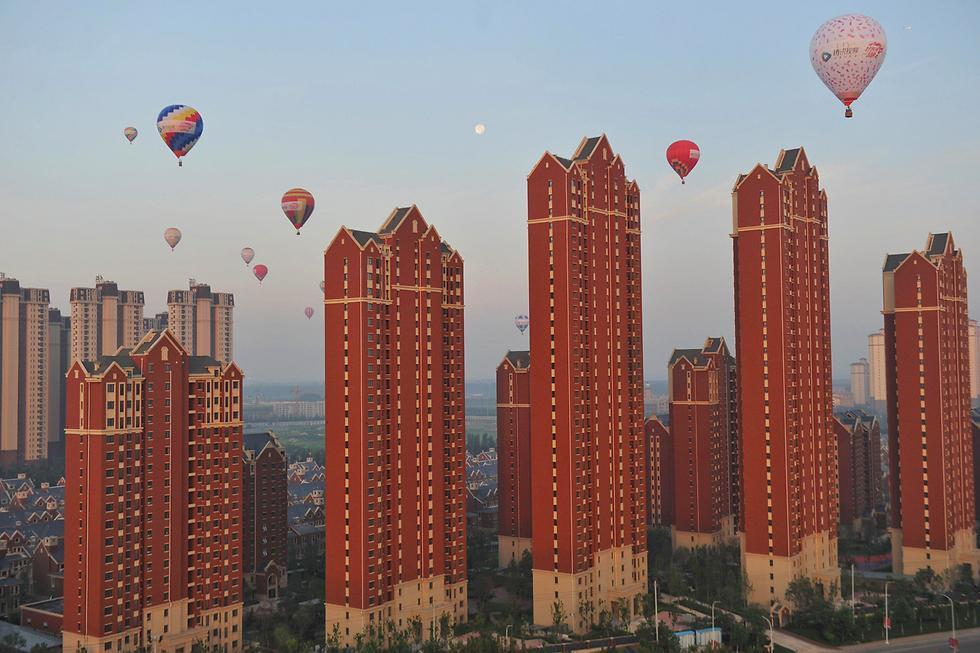 כדורים פורחים מעל בנייני מגורים בטיינג'ין בסין (צילום: רויטרס)