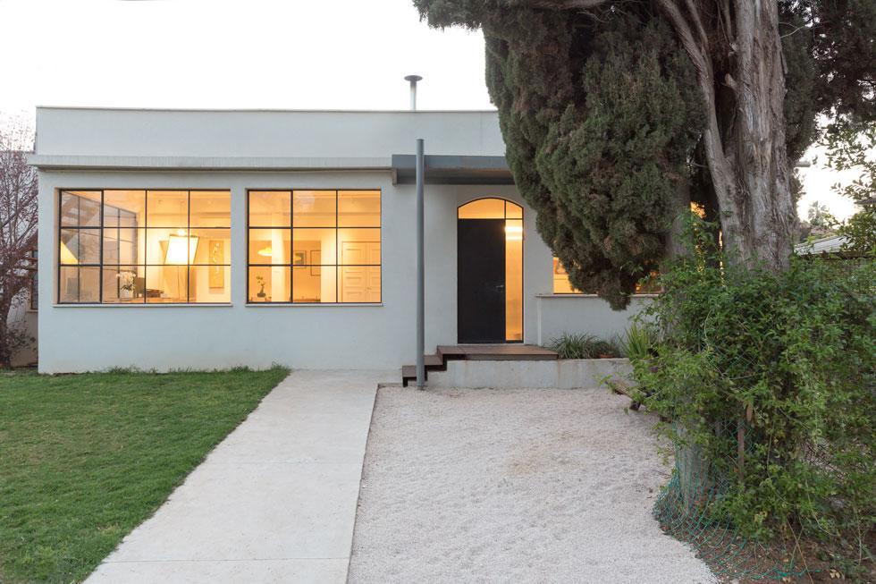 הבית בן קומה אחת, פשוט ונקי. גגון הפח בכניסה והפרזול השחור בחלונות משווים לו מראה תעשייתי-לופטי, מעין מזכרת מת''א, שממנה עברו בני הזוג (צילום: דור נבו)