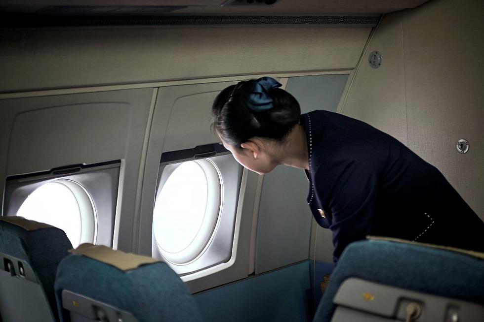 דיילת אייר קוריו מביטה בחלון המטוס (צילום: Arthur Mebius) (צילום: Arthur Mebius)