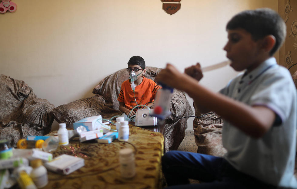 Mustafa and Mohammad Shanty, who suffer from cystic fibrosis, receive oxygen therapy during a power cut in their family house, which is equipped with a backup battery-powered system (Photo: Reuters)