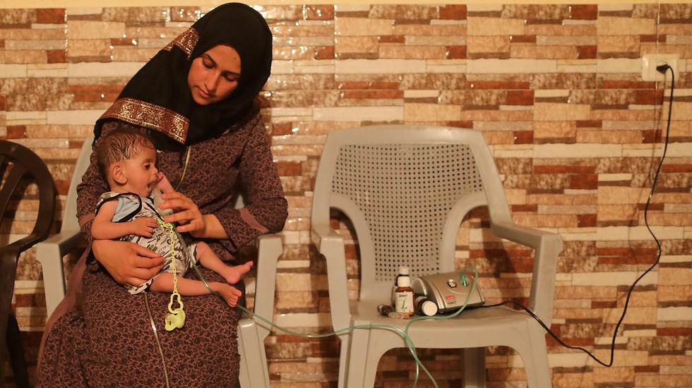 Ritta al-Jalees holding her son Fares, who suffers from cystic fibrosis, as he receives oxygen supplementation therapy inside their house in Gaza City (Photo: Reuters)