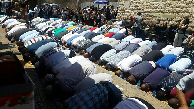 Muslim protestors pray before the Temple Mount