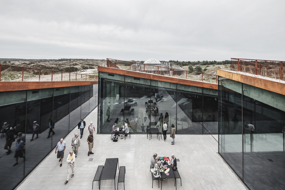 המוזיאון נחפר מתחת לדיונת חול, כדי להשתלב בסביבה - באופן שמנוגד להצבה הגסה של הבונקר המלחמתי (צילום: Rasmus Hjortshoj, Big)