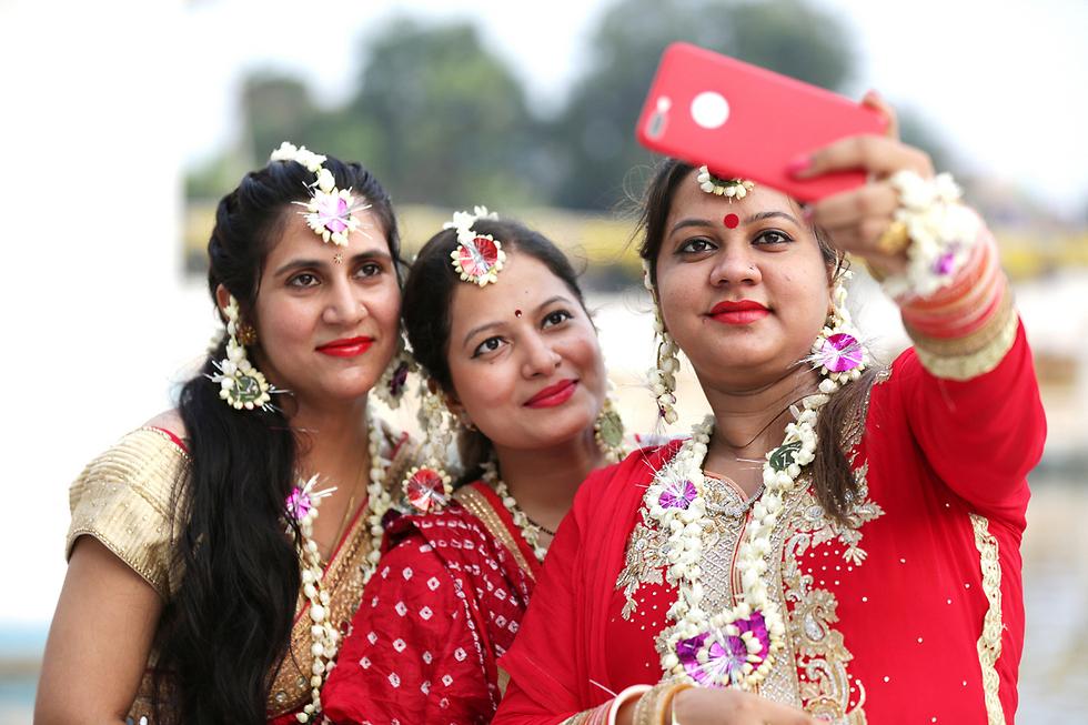 הודיות בלבוש מסורתי עושות סלפי בפסטיבל הנשים באמריסטר, הודו (צילום: EPA)