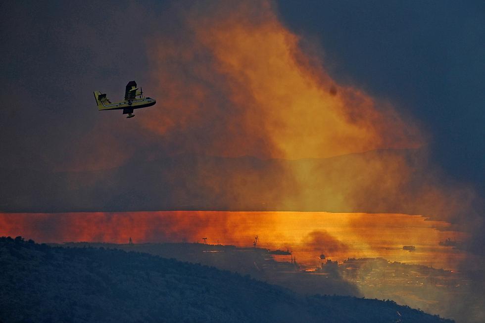 מטוס כיבוי טס מעל שריפה ליד ספליט בקרואטיה (צילום: EPA)