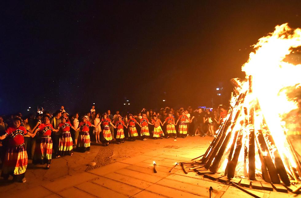 פסטיבל הלפיד של בני המיעוט האתני יי במחוז גוויג'ואו בסין (צילום: רויטרס)