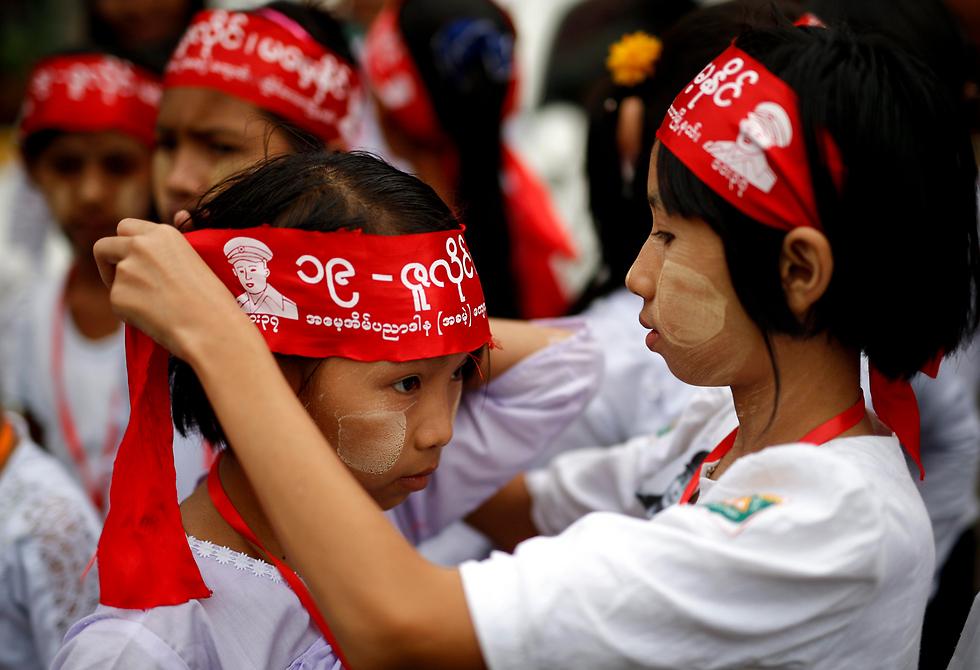 נערות קושרות סרטי ראש ביום הקדושים ביאנגון, מיאנמר (צילום: EPA)