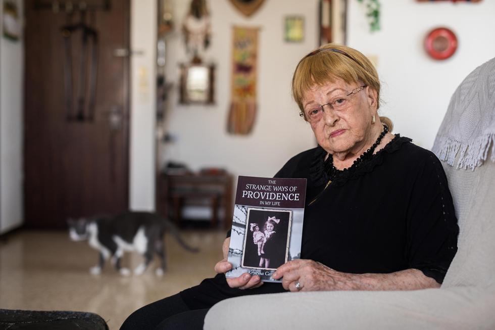 """קריסטינה כרמי עם הספר . """"כל לילה הייתי מדברת עם אלוהים ואומרת לו שאימא הבטיחה שהוא ישמור עלי"""" (צילום: טל שחר)"""