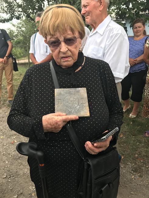 מחזיקה באריח ששרד מבית הכנסת של אוברטין (צילום: בני כרמי)