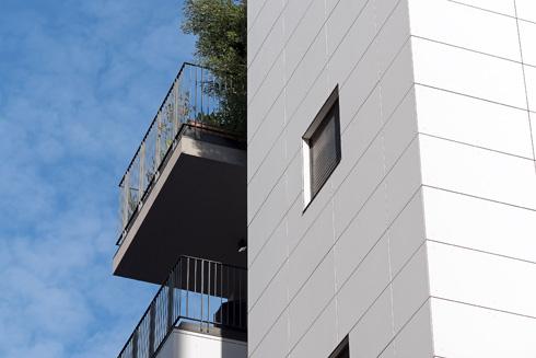 חזית הבניין החדשה מחופה בלוחות צמנט עם פסי ניתוק (צילום: עמית גושר)