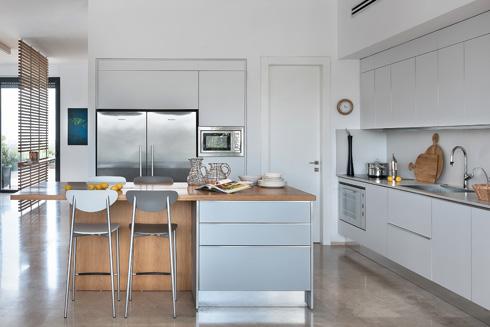 המטבח בנוי בצורת ר', ובמרכזו האי שמשמש לאחסון ולישיבה. הדלת (מימין למקרר) מובילה למטבח אחורי וחדר שירות (צילום: עמית גושר)