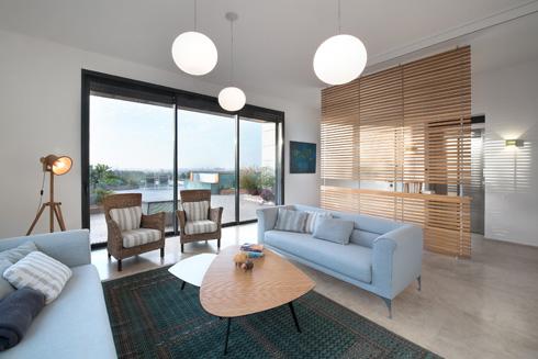 מבט מהסלון אל המרפסת המערבית. המחיצה הקלה מסרגלי העץ (מימין) מפרידה את הסלון מהכניסה לדירה (צילום: עמית גושר)