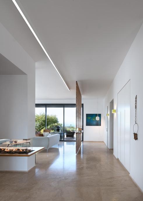 השטח הציבור בדירה מרוצף באבן טרוורטין בהירה. על הקיר (ממול) עבודת אמנות של סוזן רוס. הקמין השקוף (משמאל) נראה גם מהסלון וגם מפינת האוכל (צילום: עמית גושר)