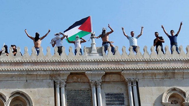 Young Muslim protestors climb al-Aqsa in protest (Photo: Reuters)