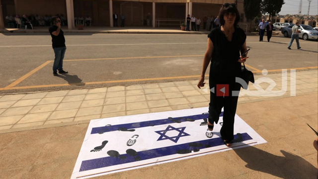 Mourners stepping on an Israeli flag on their way to the funeral