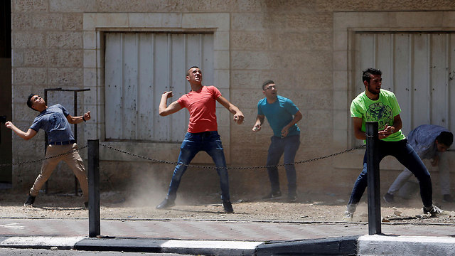 Palestinian youths throwing rocks at security forces (Photo: Reuters)