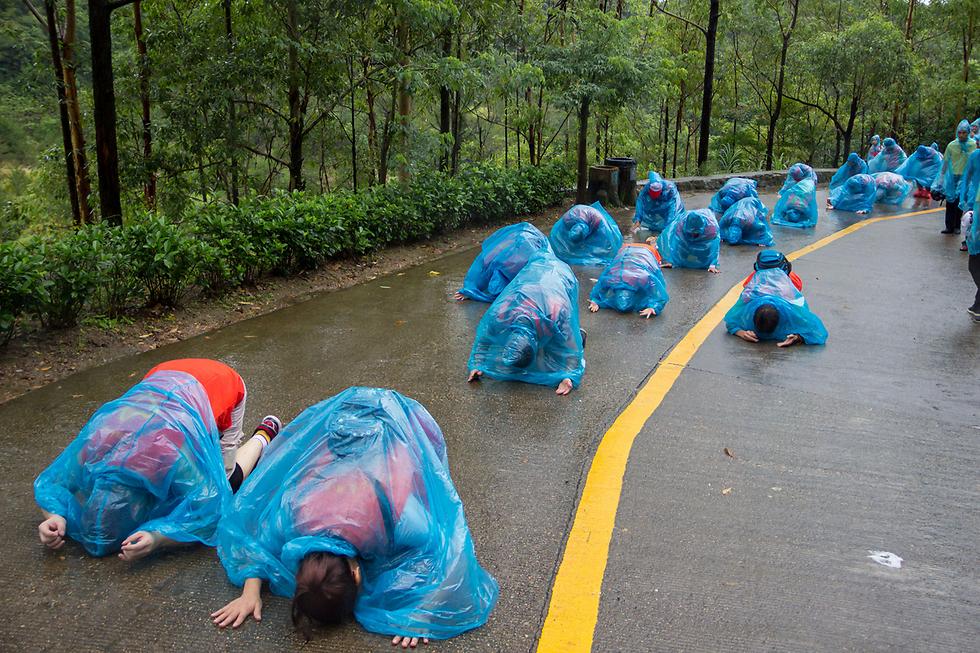 מתפללים בכריעה בגשם של הר גוואנין, סין (צילום: רויטרס)