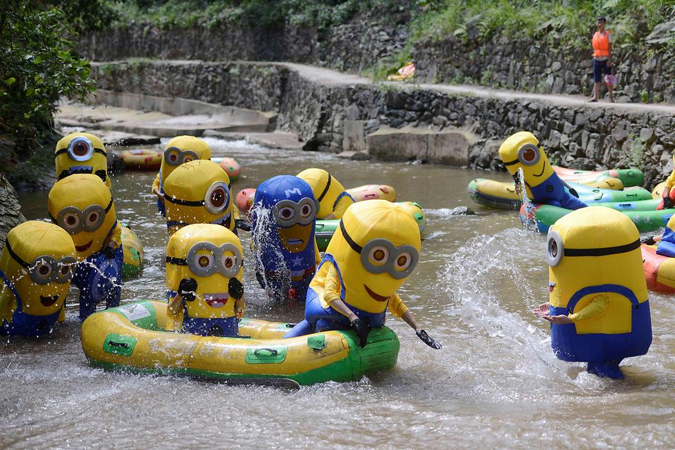 חותרים בתחפושת מיניונים בנהר בסין (צילום: רויטרס)