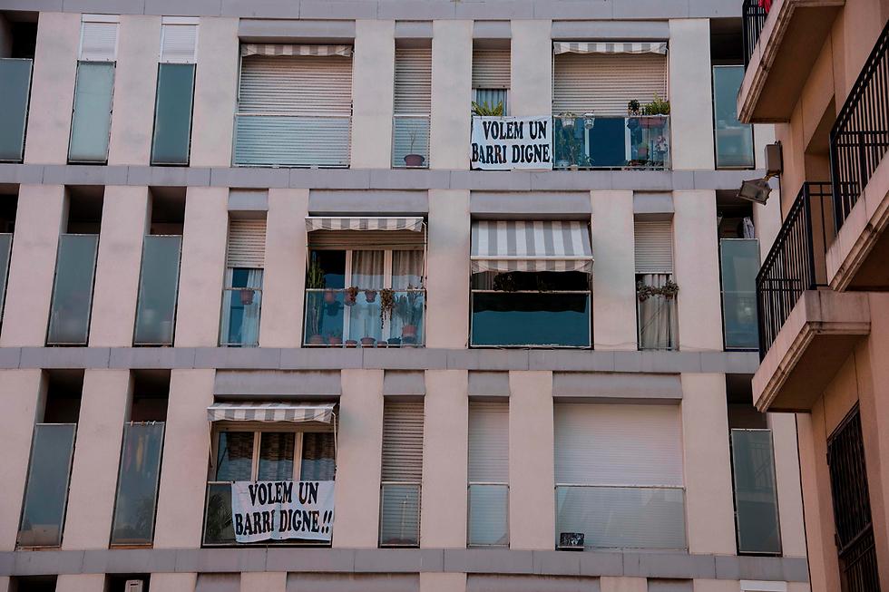 """שלטים במרפסות בברצלונה: """"רוצים שכונה צנועה"""" (צילום: AFP) (צילום: AFP)"""