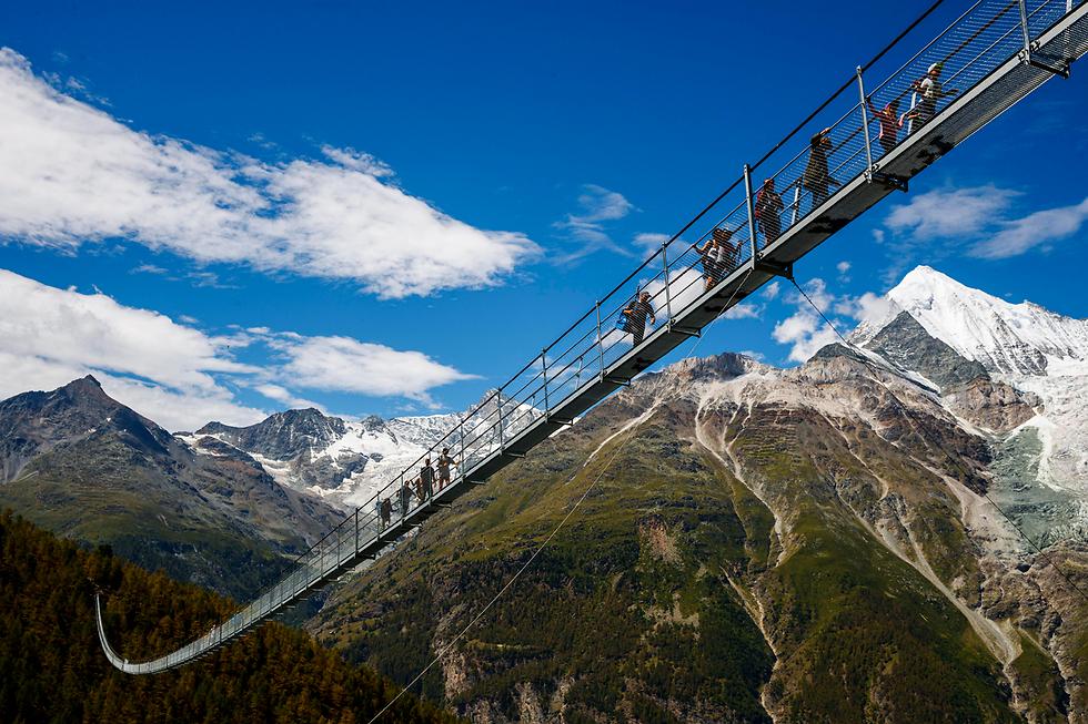 בשווייץ השיקו את הגשר התלוי הארוך ביותר בעולם להולכי רגל שנמתח לאורך 494 מטרים ונמצא בסמוך לעיירת הנופש צרמט (צילום: EPA)