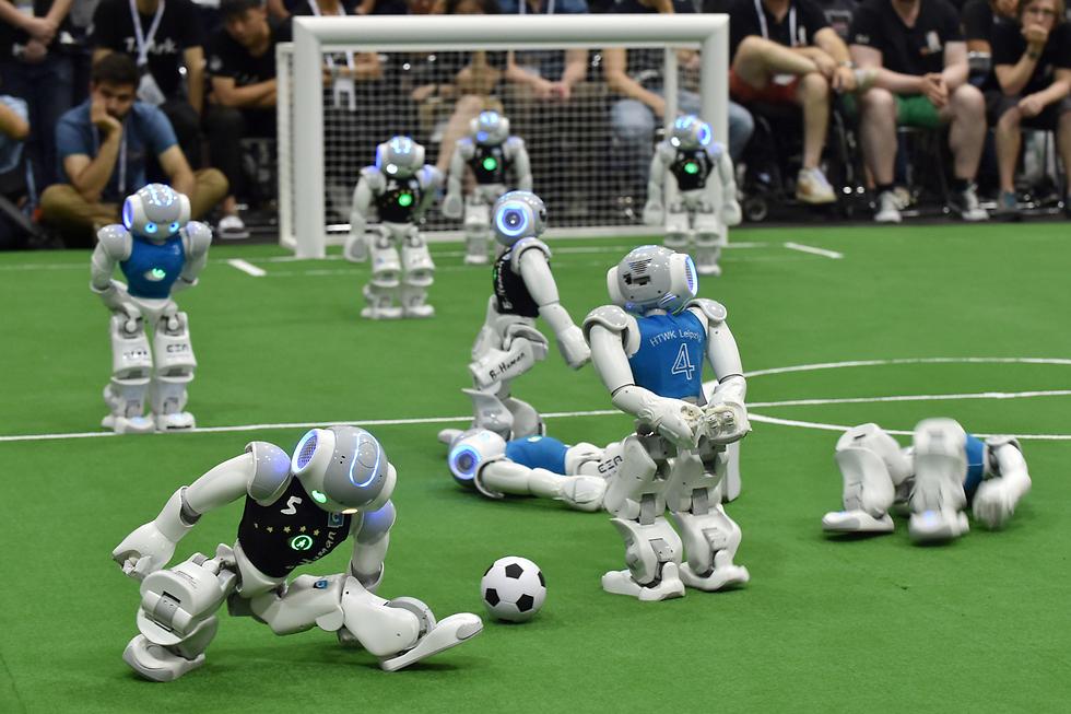 טורניר כדורגל בעיר היפנית נגויה. במקום שחקנים אנושיים - רובוטים. במקום צופים: 3,000 חוקרים וסטודנטים להנדסה שבאו לבחון את ביצועי הטכנולוגיות החדשות שלהם (צילום: AFP)