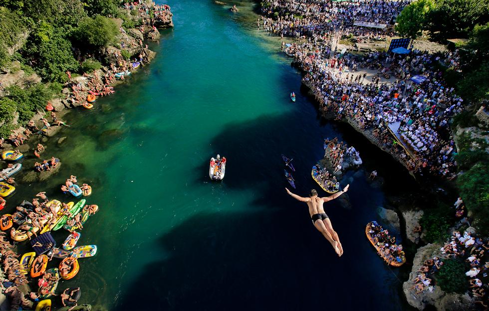 יותר מעשרת אלפים צופים הגיעו לצפות בתחרות הקפיצה למים השנתית מהגשר העתיק (שגובהו 27 מטרים) בעיר מוסטר, בוסניה הרצגובינה. באירוע, שנערך זה יותר מ-450 שנה, משתתפים 41 מתמודדים שקופצים לנהר נרטבה (צילום: AP)