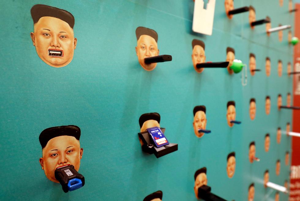 """מכשירי דיסק און קי תלויים על מתקנים בדמותו של שליט צפון קוריאה קים ג'ונג און בכנס האקרים בלאס וגאס. ארגון זכויות האדם """"דיסק קון קי לחופש"""" תלה את המכשירים, שאותם הוא נוהג לתרום לצפון קוריאנים כדי שיבריחו מידע אל מחוץ לארצם (צילום: רויטרס)"""
