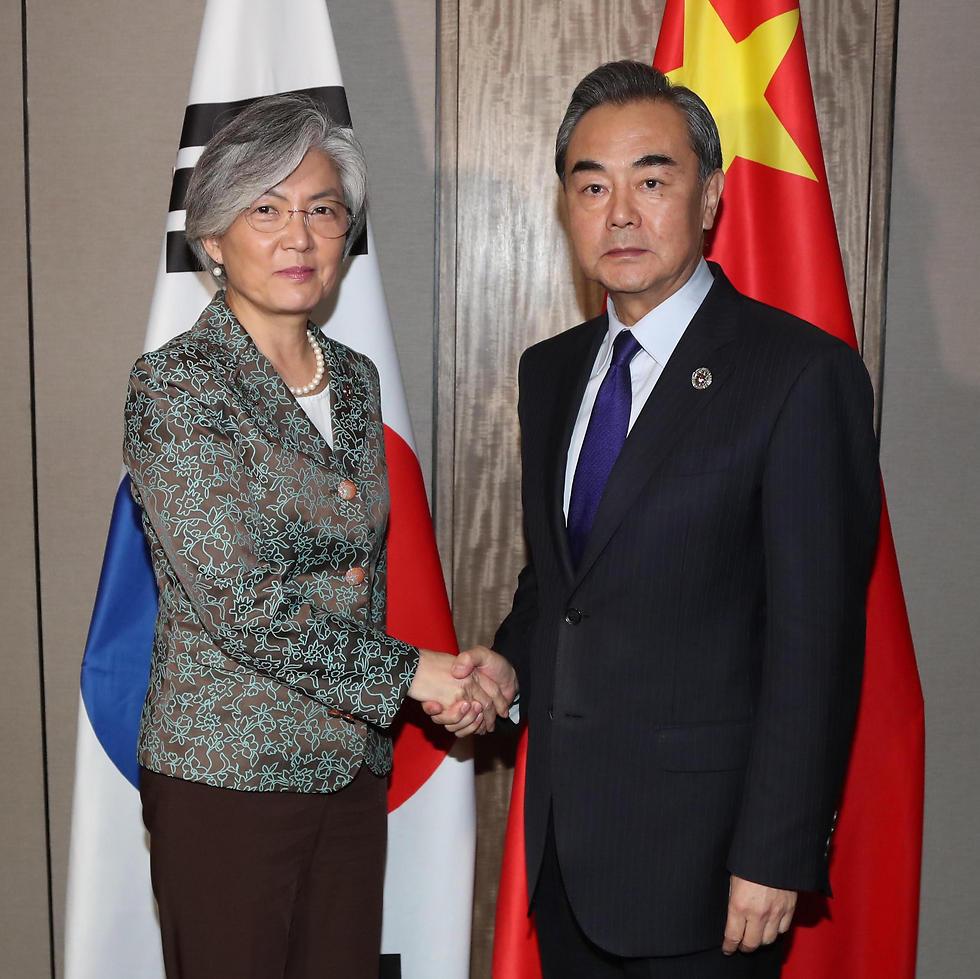 שר החוץ הסיני ומקבילתו הדרום-קוריאנית בפגישה בשולי הוועידה (צילום: EPA)
