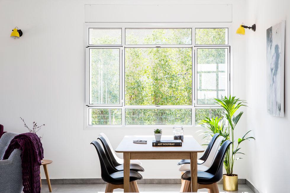 פינת האוכל לצד החלון הפונה לגינת הצד. המעצבת כרמית גת-בוצר התאימה את גודל החלונות והוויטרינות בשלב בניית הבית במפעל (צילום: איתי בנית)