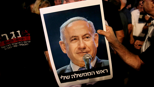 A supporter of Netanyahu's holding a photo of his that reads, 'My prime minister' (Photo: EPA)