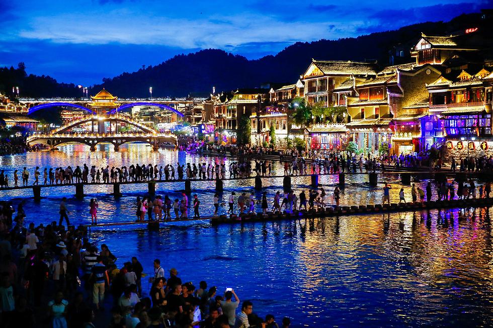 עונת התיירות הגיעה לעיר העתיקה פנגהואנג שבסין (צילום: AFP)
