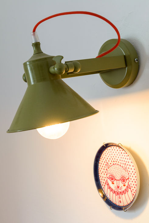 מנורת חאקי מאירה מעל צלחת מאוירת של יפעת פטררו (צילום: אדריאן דודה)