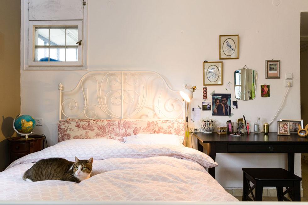 חדרם של בני הזוג מרווח מאוד, ונהנה משלושה כיווני אוויר ומרפסת פרטית. מיטת ברזל לבנה של איקאה שודרגה באמצעות ראש מיטה מרופד (צילום: אדריאן דודה)