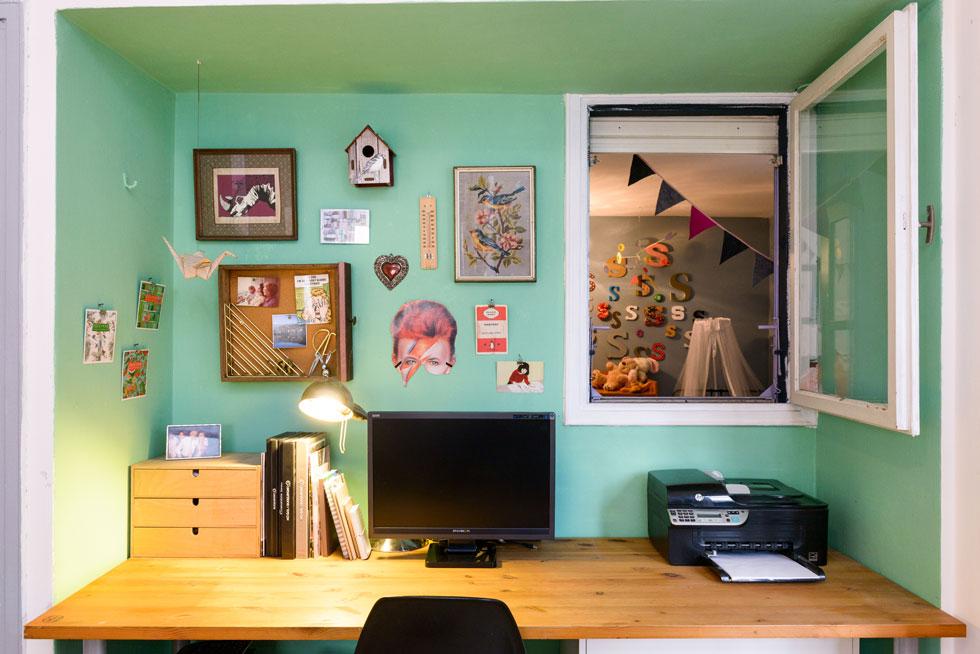 פינת עבודה מוקמה מתחת לחלון קטן שמחבר בין חדר ההורים לחדר הילדים. הקיר נצבע בירוק בהיר, וקושט באוסף של זכרונות מפרויקטים, תקופות ומקומות שונים (צילום: אדריאן דודה)