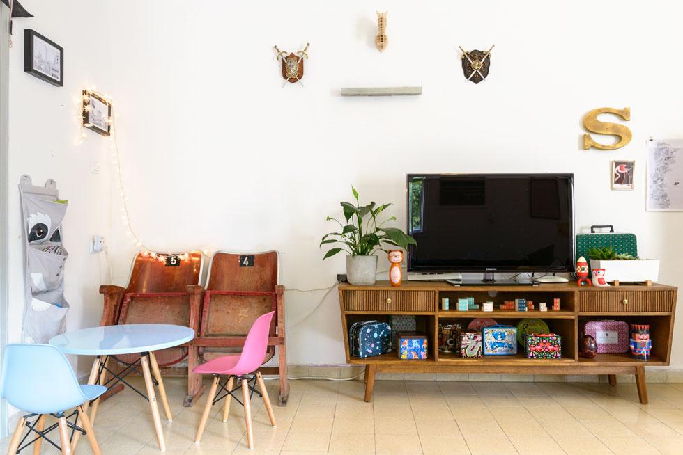 כסאות ישנים מקולנוע מוגרבי עליו השלום, יחד עם פינת יצירה, נמצאים במעבר בין הסלון לחדרו של נבו הקטן (צילום: אדריאן דודה)