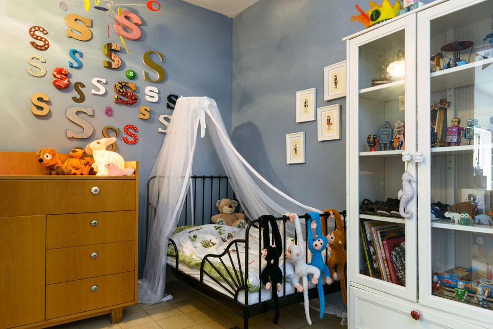 במרכז ארון ויטרינה עם אוסף של צעצועי פח, ובצד השני מיטה עם כילה (צילום: אדריאן דודה)