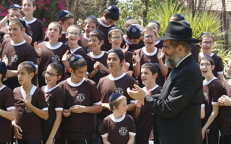 """""""מגיל אפס מתחנכים על ויתור עצמי"""". הרב אהרונוב עם ילדי הקייטנה (צילום: שמולי הרשקופ)"""
