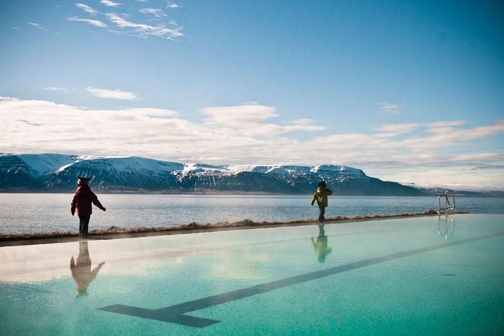 בריכת השחייה הציבורית בכפר הדייגים הקטנטן הופסוס בנויה סמוך לקצה מצוק, במדרון המגן מרוחות הצפון. מי הבריכה הם מי מעיינות חמים (צילום: © Rafn Sigurbjornsson)