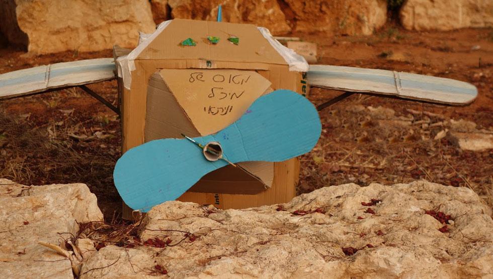מטוס בעל מדחף מסתובב, העשוי מגליל מגבות נייר והציר ממכחול ישן (צילום: נדב שטרית)