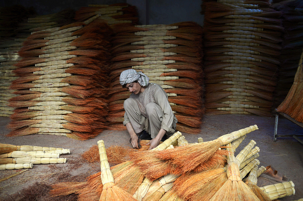 בעל חנות מסדר מטאטאים באפגניסטן (צילום: AFP) (צילום: AFP)