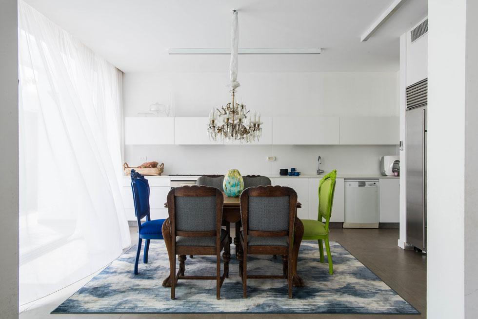 במרכז המטבח העכשווי פינת אוכל עם שולחן וכסאות עתיקים שרופדו ונצבעו מחדש. את הנברשת העתיקה קיבלה בעלת הבית במתנה מלקוח  (צילום: יוגב עמרני)
