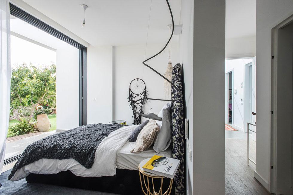 """חדר ההורים פונה אל הגינה האחורית. המיטה צמודה לקיר ההדף של הממ""""ד, המשמש כחדר ארונות  (צילום: יוגב עמרני)"""