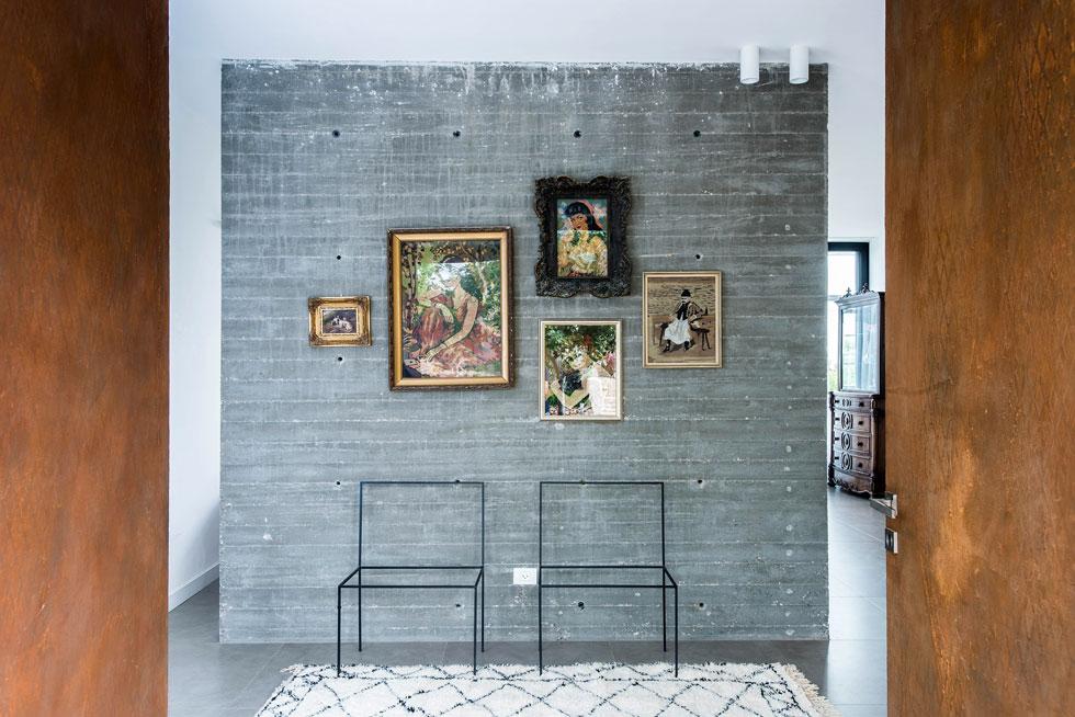 דלת הכניסה נפתחת אל מבואה עם קיר בטון חשוף, שעליו תלתה הורוביץ-חורש אוסף תמונות גובלן עם מסגרות מקוריות, שהובאו מבית סבתה (צילום: יוגב עמרני)