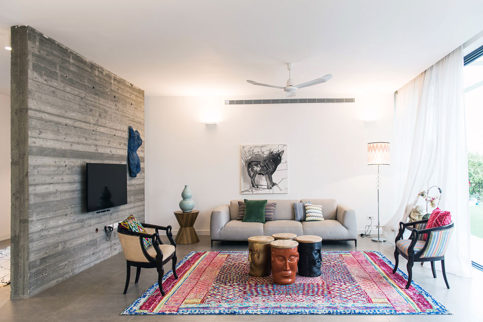 עיצוב הסלון החל בבחירת השטיח. הריהוט הותאם אליו, ולא להיפך, כמקובל. על הקירות ציור של ליה נברו, וטורסו שפיסל אולג קולקין (צילום: יוגב עמרני)