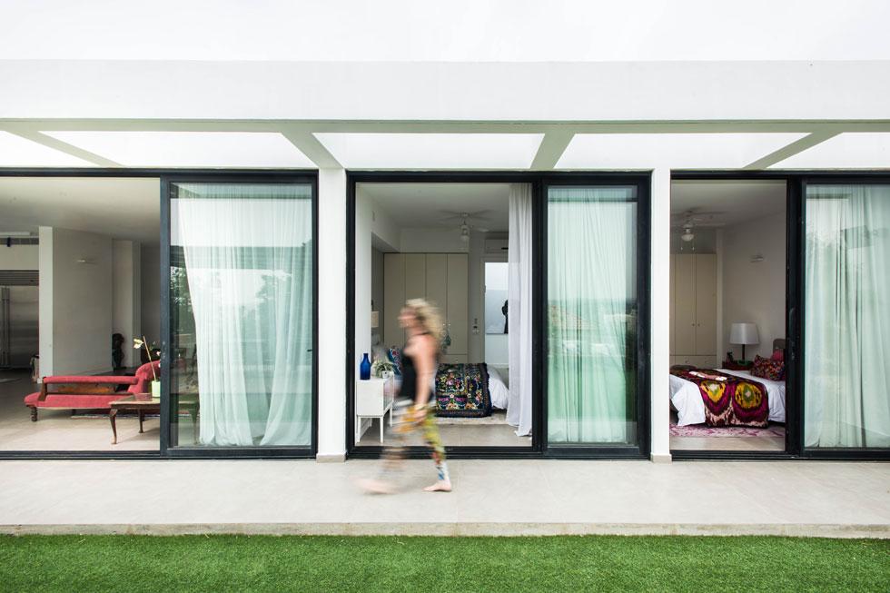 מבט מהגינה האחורית אל החדרים שנפתחים אליה, כמו מסגרות של תמונות. מימין: חדרי הבנות, משמאל: הסלון  (צילום: יוגב עמרני)