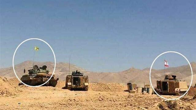 Two tanks, one with a Hezbollah flag (L) and one with a Lebanese flag
